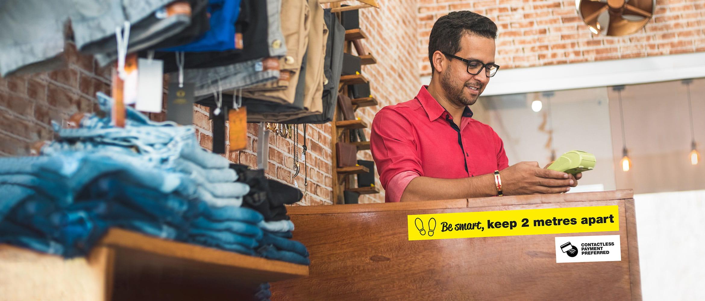 muž za pokladňou v maloobchodnom prostredí, označenie pokladne Brother štítkami
