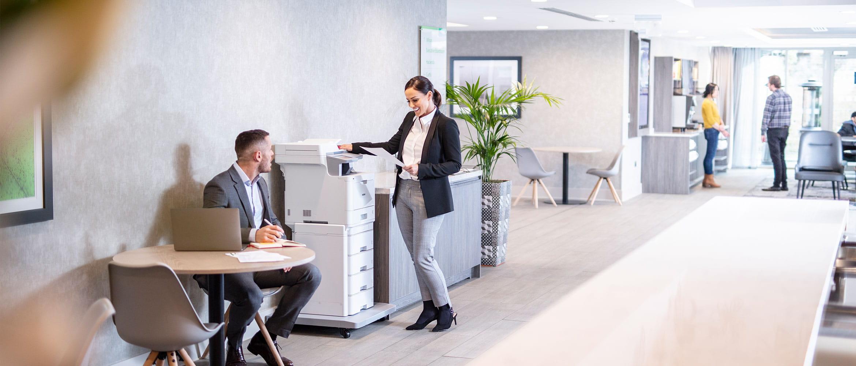 Žena v saku pri farebnej laserovej tlačiarni Brother MFC-L9570CDWTT, muž sediaci pri stole s laptopom, ľudia v pozadí