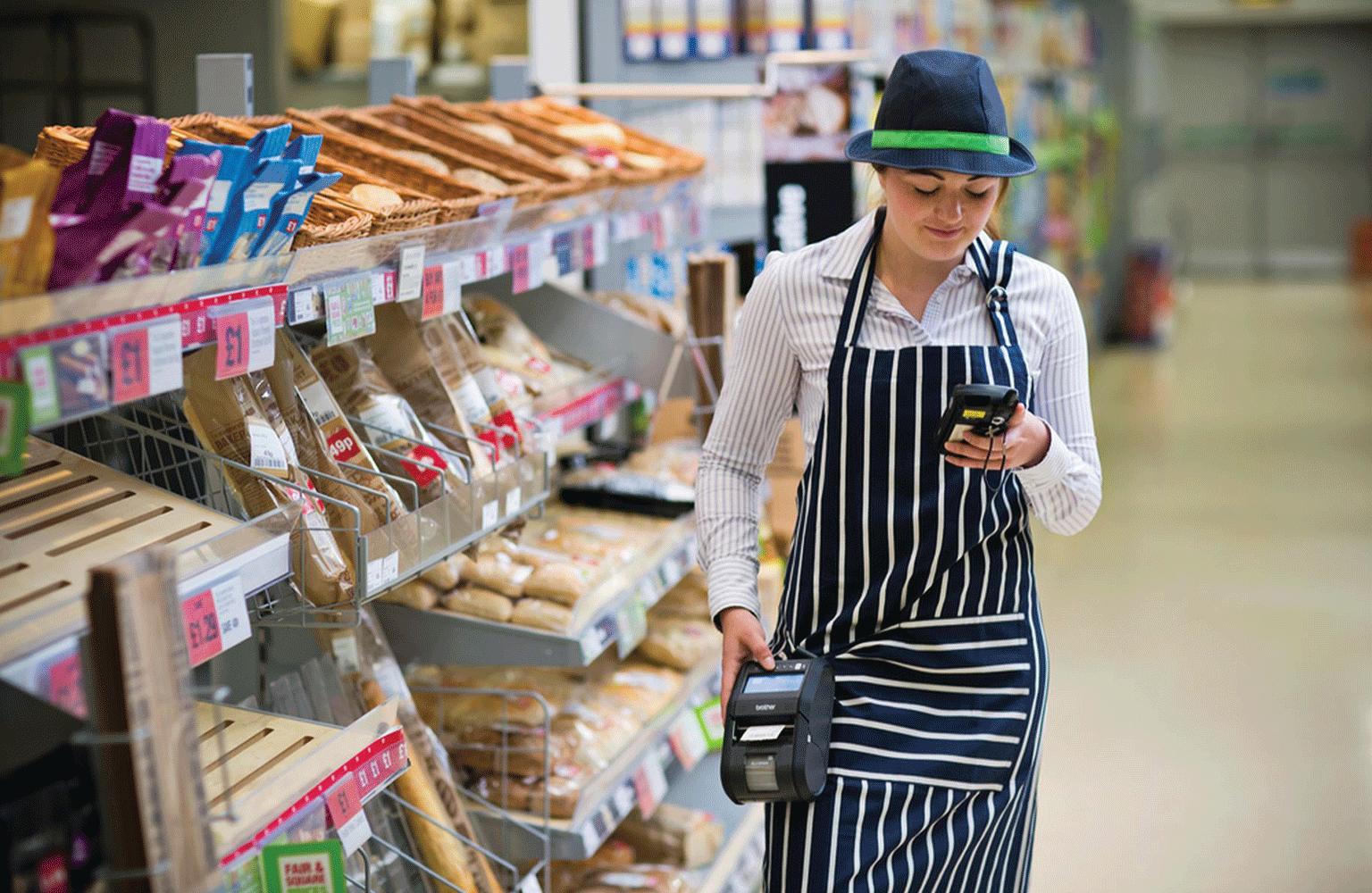 predavačka v obchode kráčajúca s pripnutou RJ tlačiarňou štítkov
