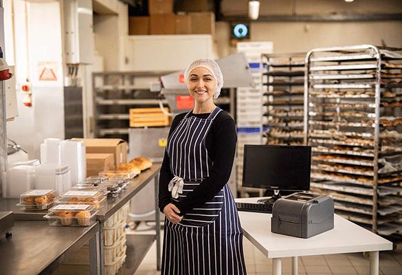 usmievajúca sa pracovníčka v závodnej kuchyni stojaca vedľa Brother tlačiarne TD-4T