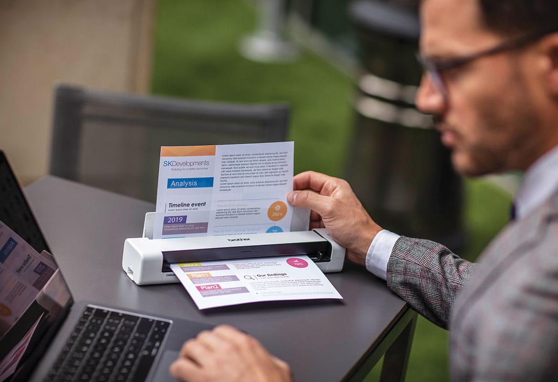 muž v okuliaroch s laptopom skenujúci dokumenty