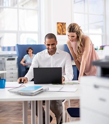 žena a muž s laptopom rozprávajúci sa v kancelárii