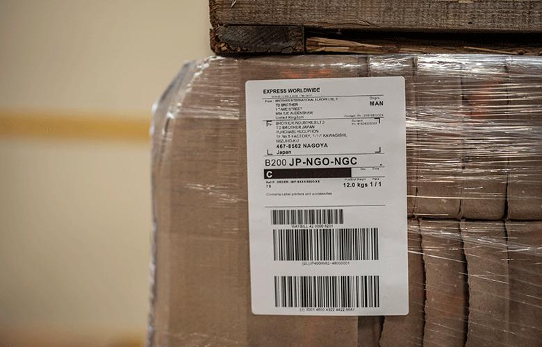 detail prepravného štítku nalepeného na krabici