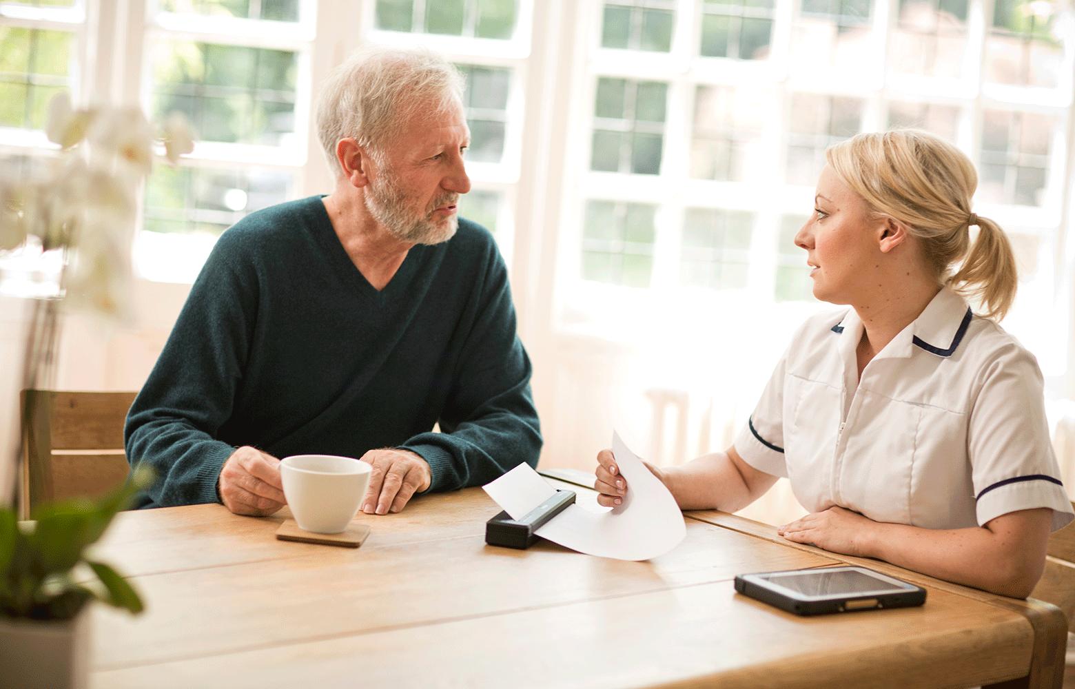 muž a zdravotná sestra sediaci pri stole, tlačiareň PJ tlačiaca dokumenty