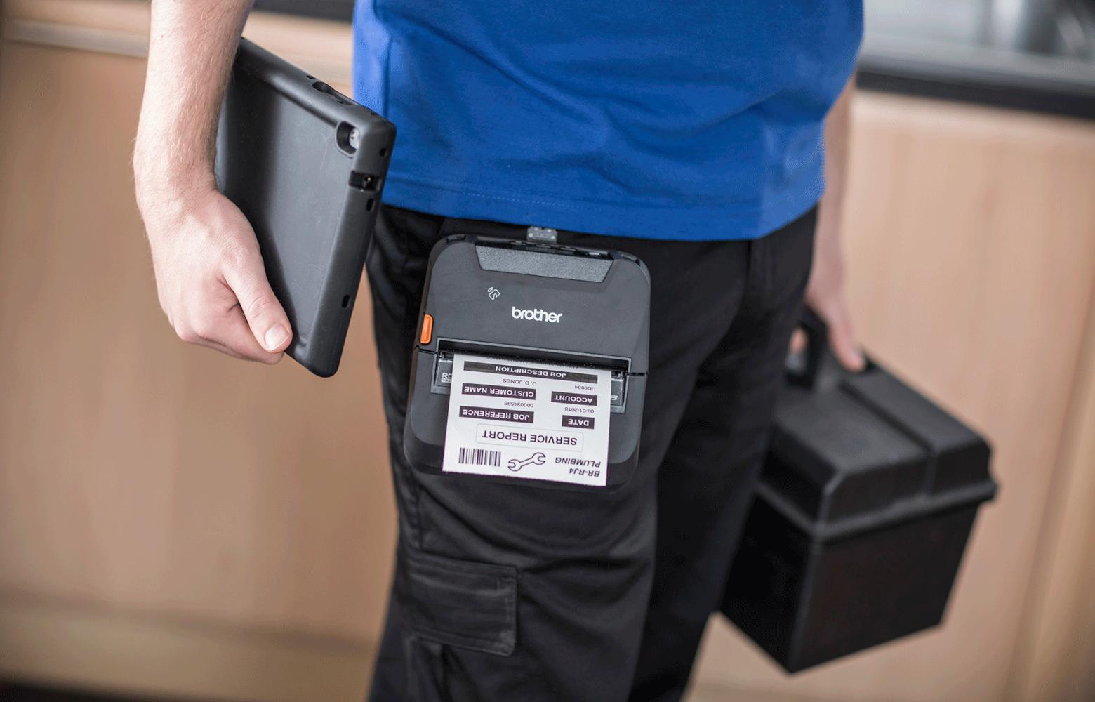 pracovník držiaci tablet s tlačiarňou RJ pripnutou na opasku