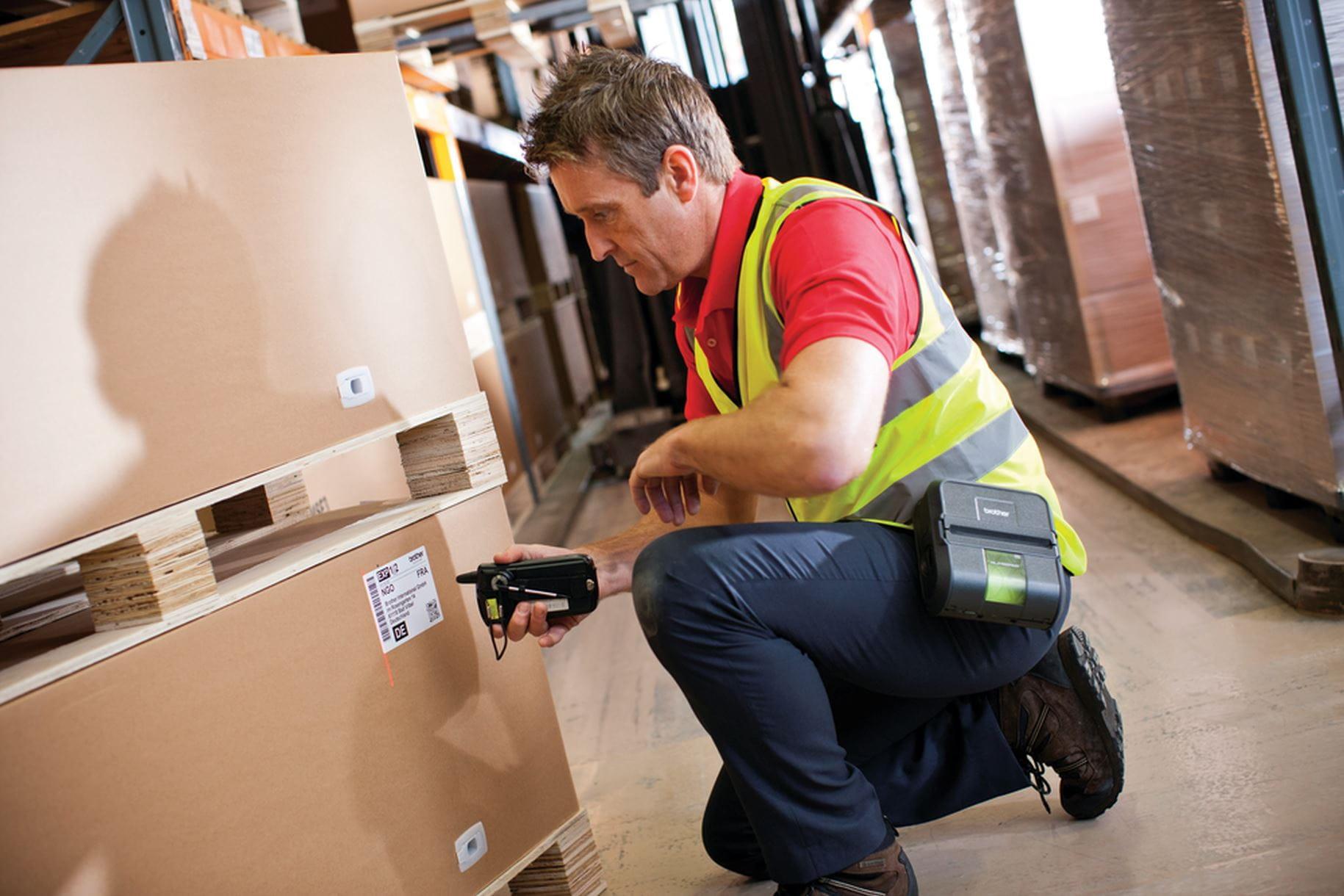 pracovník v sklade skenujúci štítok na krabici s Brother RJ za opaskom