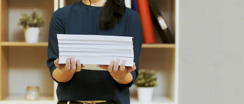 Žena drží v rukách stoh papiera