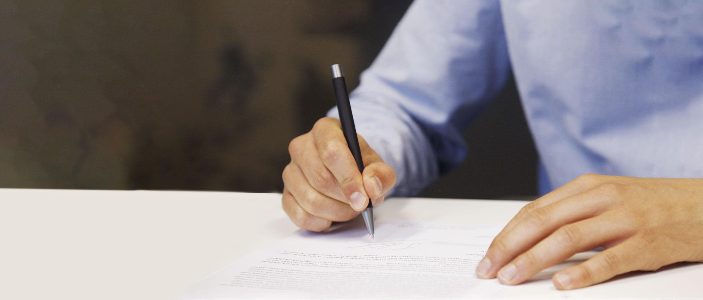 Muž v modrej košeli podpisuje dokument