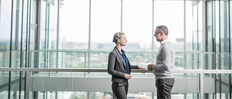Muž a žena sa rozprávajú na balkóne administratívnej budovy