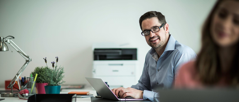 Muž za stolom s laptopom a tlačiarňou v pozadí