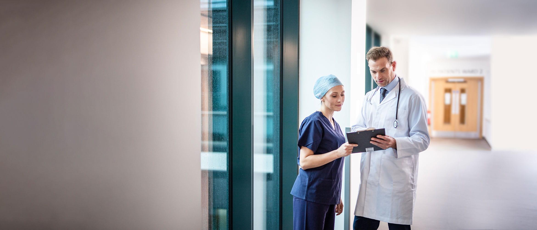 Lekár v bielom plášti so stetoskopom s lekárkou v chodbe nemocnice