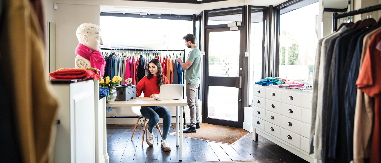 Muž nakupujúci oblečenie a žena sediaca pri stole, pri tlači dokumentu v obchode s odevmi