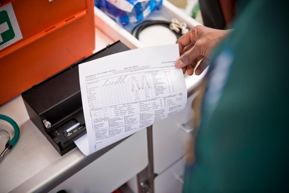 muž tlačí A4 dokument v sanitke