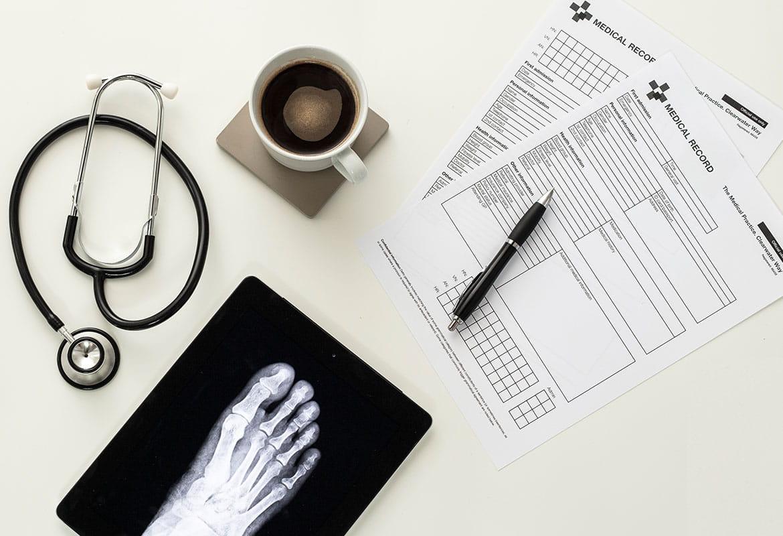 Lekárske dokumenty, pero, šálka kávy, stetoskop, tablet s röntgenom chodidla na bielom stole