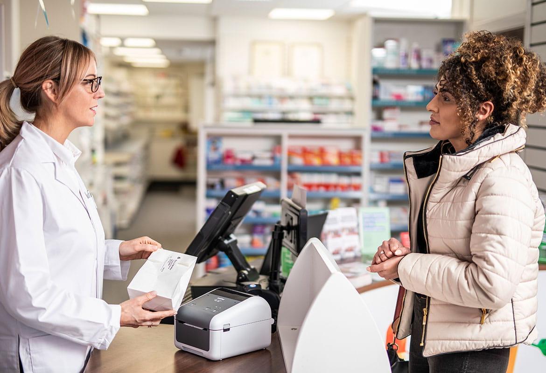 Lekárnička v okuliaroch za pultom obsluhuje zákazníčku s kučeravými vlasmi v kabáte