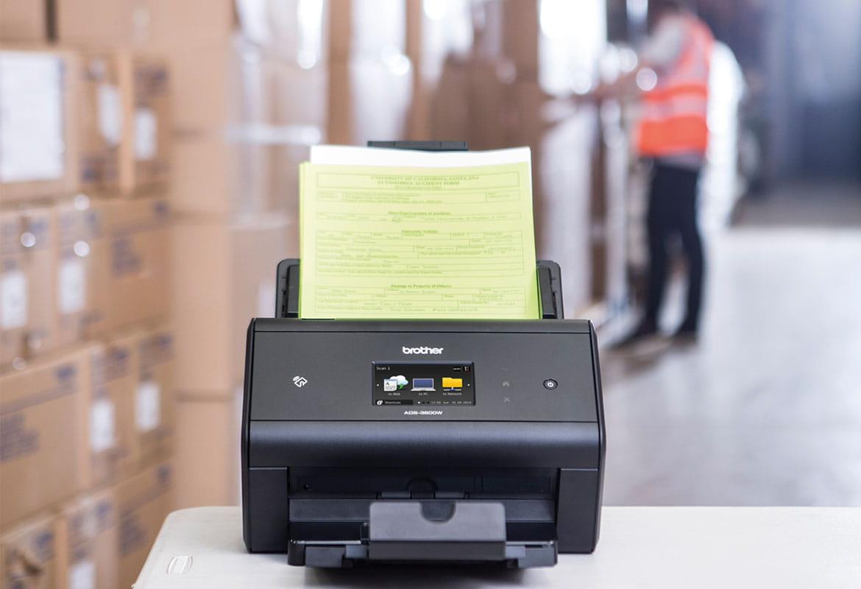 Stolný skener Brother ADS-3600W na stole archivujúci expedičné poznámky v sklade, krabice, muž v reflexnej veste