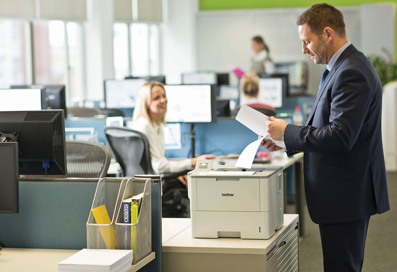 Muž v obleku stojaci pri tlačiarni držiaci papier, monitory, žena, kancelária, stôl