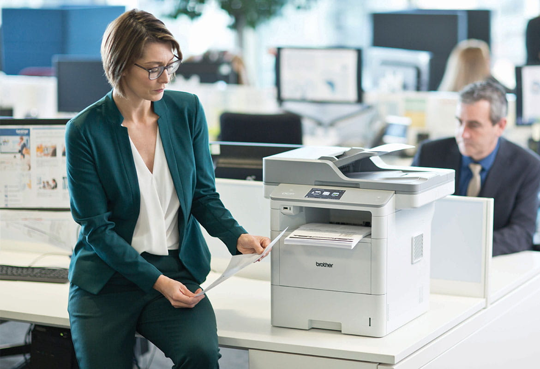 Žena v okuliaroch, v zelenom saku a nohaviciach sediaca na stole vedľa tlačiarne Brother MFC-L6900DW, muž v saku, monitory, stoly