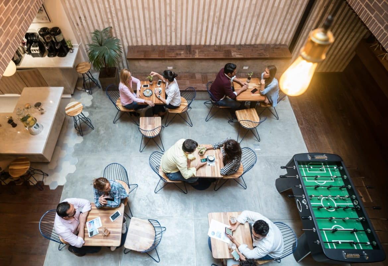 Pohľad na pracovisko budúcnosti z výšky - na elegantnú, minimalistickú kanceláriu s hotdeskmi a hracím stolom.