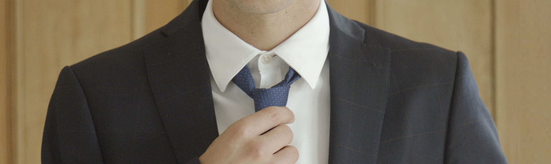 Muž v obleku si uťahuje kravatu