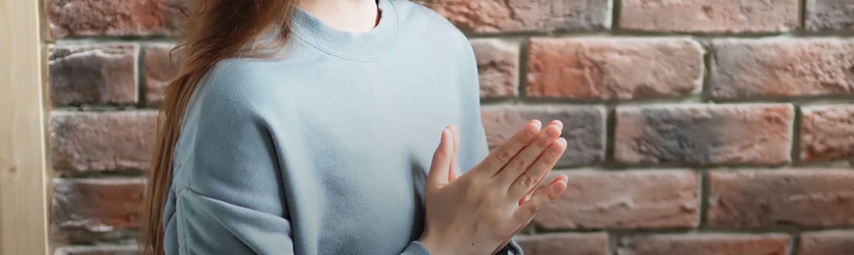 Žena v modrom so spojenými rukami