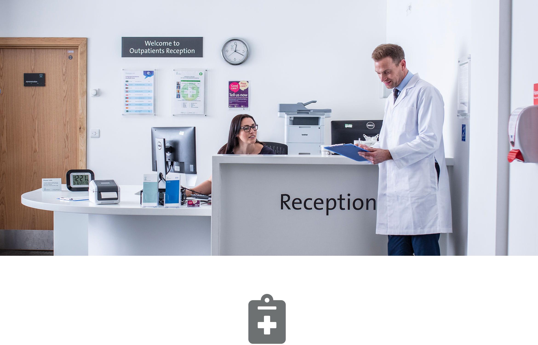 Recepčná na recepcii v nemocnici hovoriaca s lekárom v bielom plášti držiacim dokumenty, ikona klipovej dosky