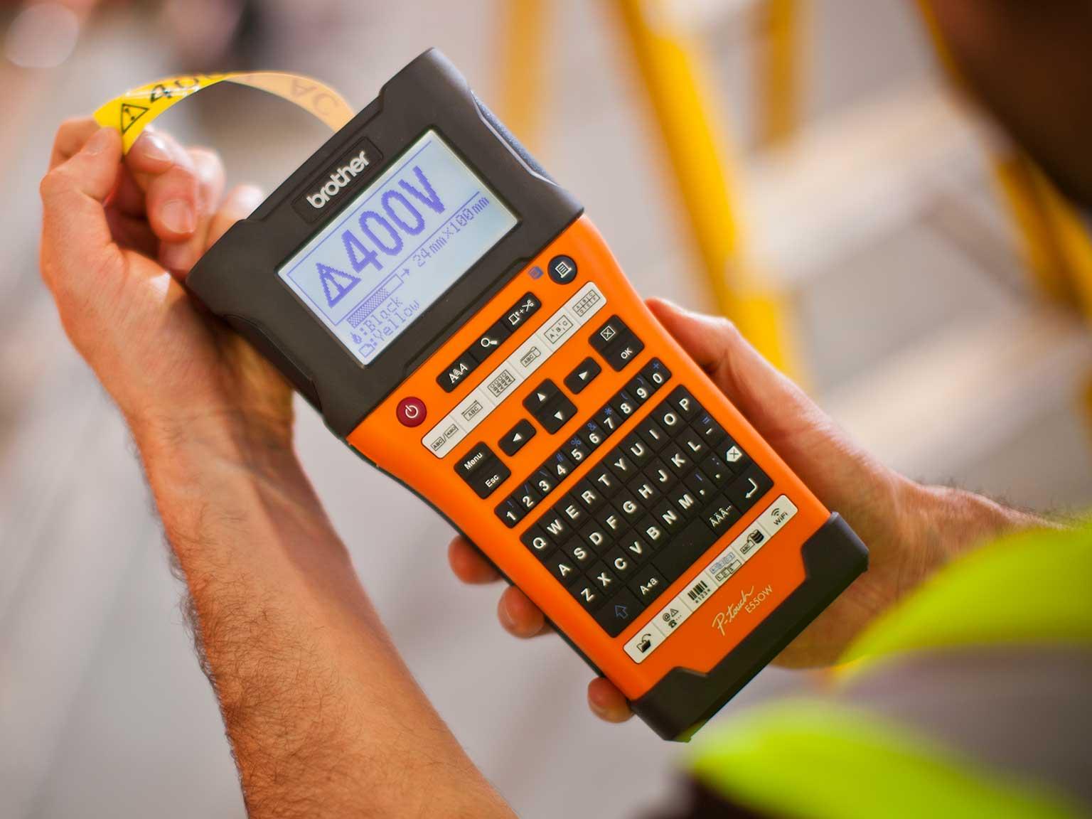 Inštalatér drží v ruke tlačiareň štítkov Brother P-touch E550