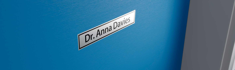 Štítok Brother čierna na striebornej s menom lekára, nalepený na dverách