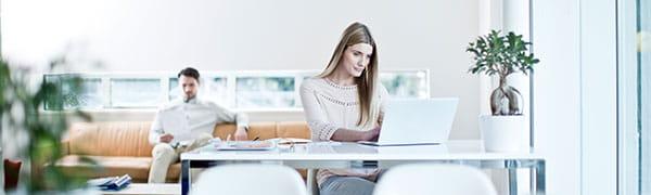 žena sedela pri stole na notebooku