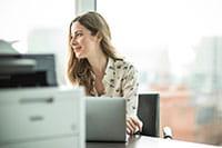 Žena za stolom v kancelárii, v popredí tlačiareň.