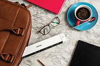 Brother DS-640 prenosný skener dokumentov, káva, okuliare, púzdro na laptop, ceruzka, tablet, ružový diár