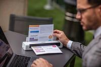 Muž v sivom obleku s okuliarmi sediaci pri stole s laptopom a  Brother DS740D prenosným skenerom dokumentov s dokumentom vo vnútri skenera