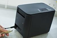 Človek ide pripojiť USB kábel do tlačiarne Brother PT-P900